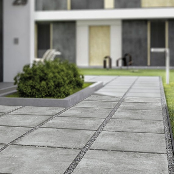 Closeup of gray, stone look, 2CM porcelain pavers set in gray gravel.