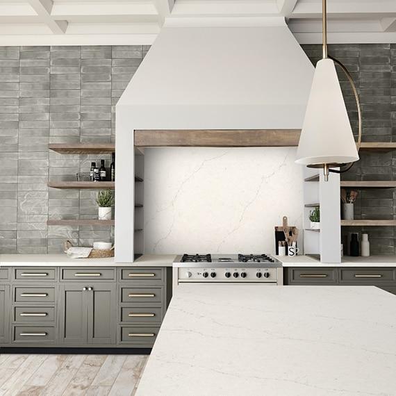 Modern farmhouse kitchen with off-white quartz island countertop and stovetop backsplash, natural wood floating shelves on gray subway tile.