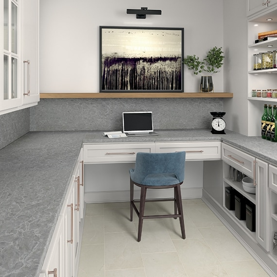 Home office with built-in desk & shelves, stone look gray quartz countertops, white cabinets, wood floating shelf, blue velvet chair, and open laptop.
