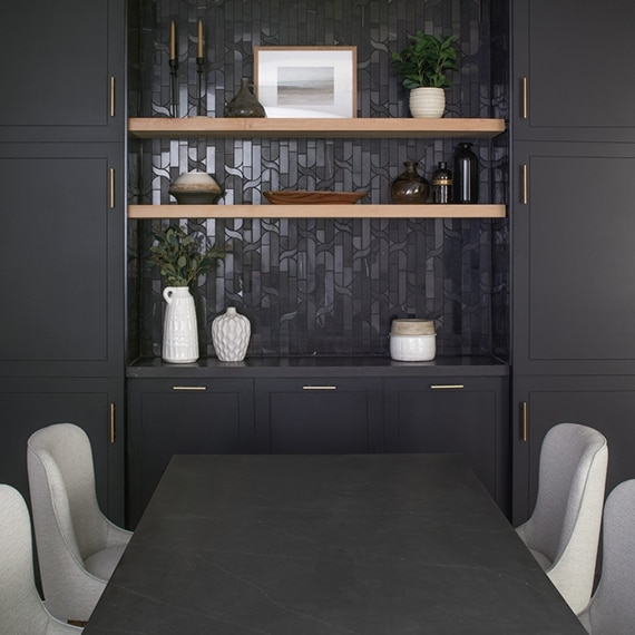 Black built-in cabinets with black marble mosaic backsplash and natural wood floating shelves in front of black quartz table with gray chairs.