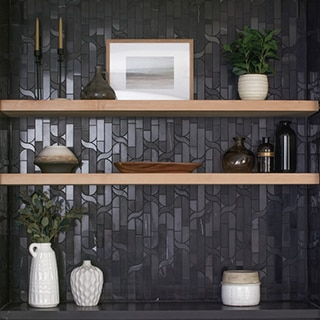 Black marble mosaic backsplash with black marble countertop, natural wood floating shelves with white vases, gold candles, print of ocean scene.