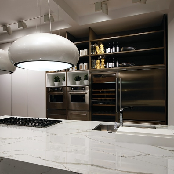 Kitchen island with sink, stove top, and white marble look quart countertop, pendant lighting, stainless steel refrigerator and double oven.