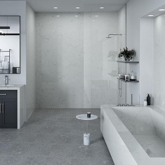 Modern bathroom design with white with gray veining quartz slab vanity countertop, shower walls, bathtub, and backsplash, and gray concrete look floor tile.