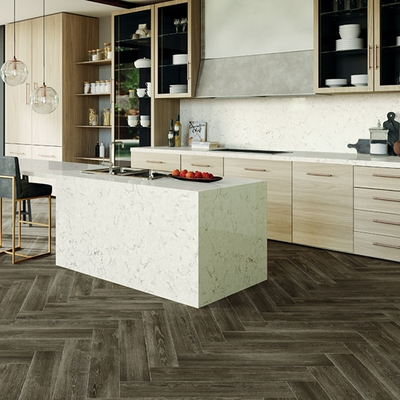 Kitchen with herringbone floor tile that looks like wood, off-white quartz with gray veining on island, countertops, and backsplash, and wood cabinets with open shelves.
