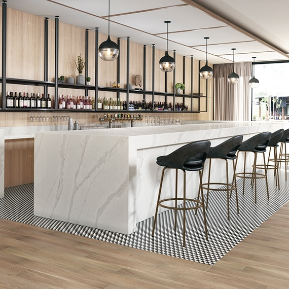 Hotel bar with white & gray marble look quartz countertops, black & white checkered tile mat set in wood look tile flooring, and racks holding wine bottles in front of wood panel wall.