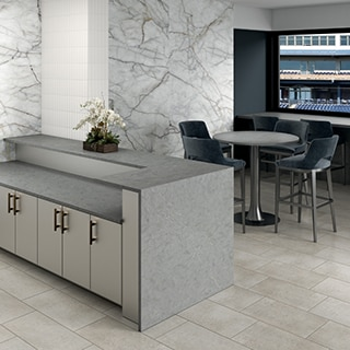Stadium suite with beige stone look floor tile, gray quartz waterfall countertop, walls covered with porcelain slab that looks like white marble with gray & gold veining.