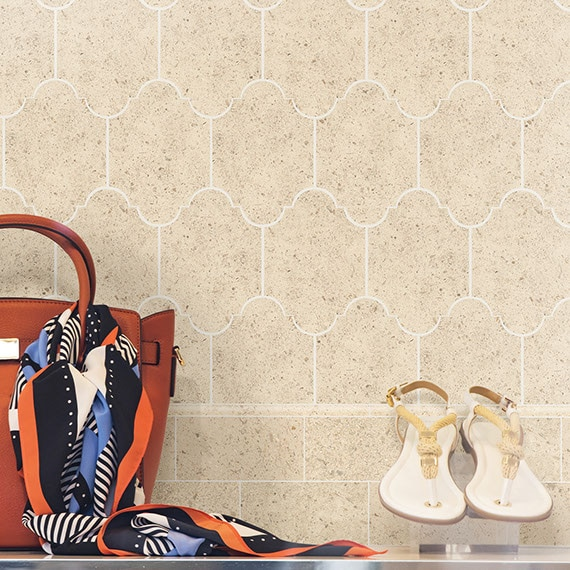 Beige limestone lantern or arabesque shaped mosaic feature wall in a retail store with shoes, bag and scarf in the foreground.