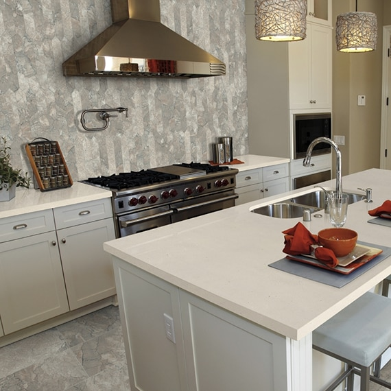 Elegant kitchen features picket marble backsplash behind stainless stain gas stove & hood, and marble floor tile, quartz countertops & island.