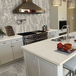 White kitchen with stainless appliances and accents and a grey and white natural stone picket-shaped mosaic on the backspalsh spanning from the countertop to the ceiling.