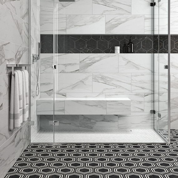 Shower with white penny round shower floor tile, white & gray wall tile that looks like marble, niche with black hexagon tile, and black & white hexagon bathroom floor tile.