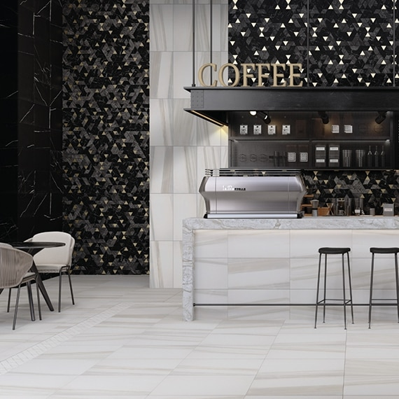 """Coffee shop with 12x24, white & beige marble floor tile, black mosaic wall tile, marble countertop, """"Coffee"""" sign suspended from the ceiling."""