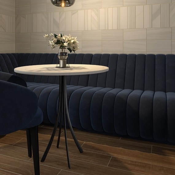 Navy velvet tufted booth and chair with table, wood look flooring, and marble tile wall.