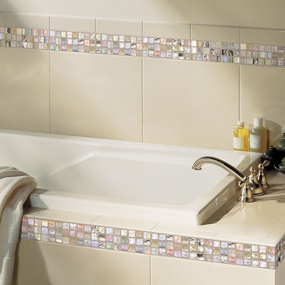 Close up of a bathroom tub and tile surround with twelve inch white tile and iridescent one inch mosaic horzontal stripe accent.
