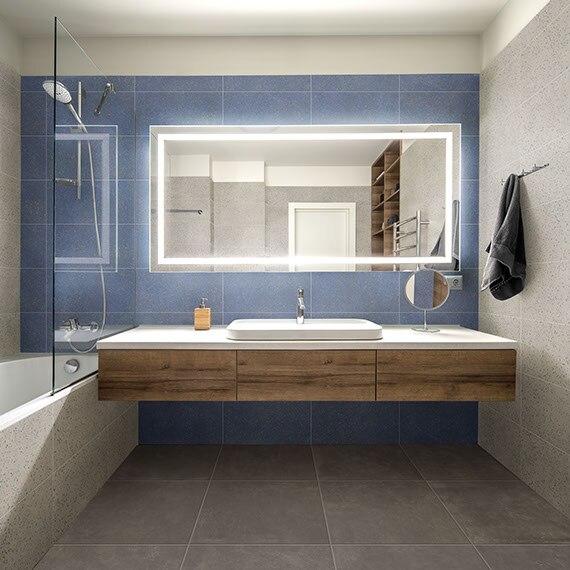 Bathroom with gray terrazzo look tile floor, floating natural wood vanity, vessel sink, blue terrazzo look tile backsplash, and lighted mirror.