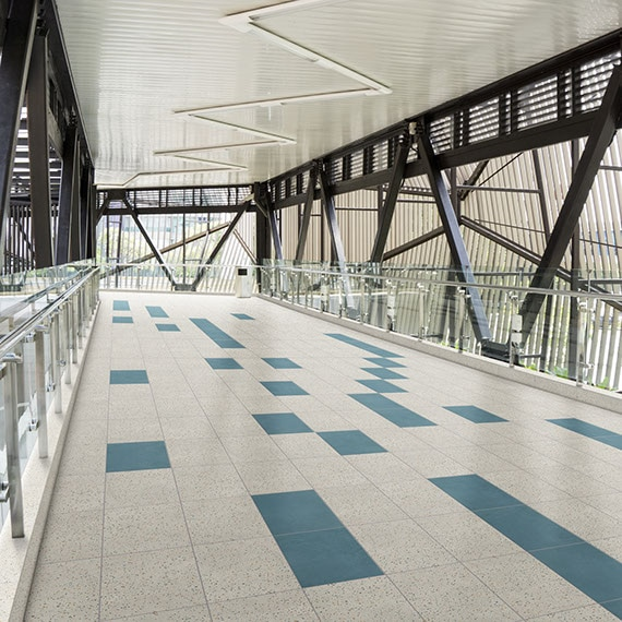 Interior of skywalk with gray and blue concrete look floor tile, glass & metal railing, black metal rafters and beams.
