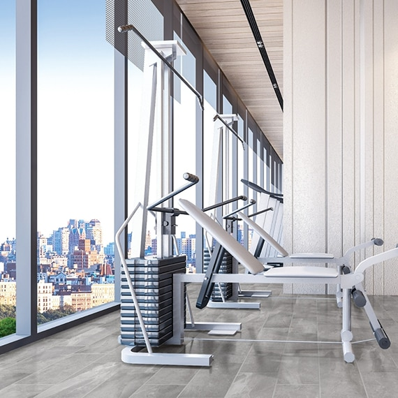Gym with weight machines, 12x24 gray marble look floor tile, and floor-to-ceiling windows with view of city skyline.