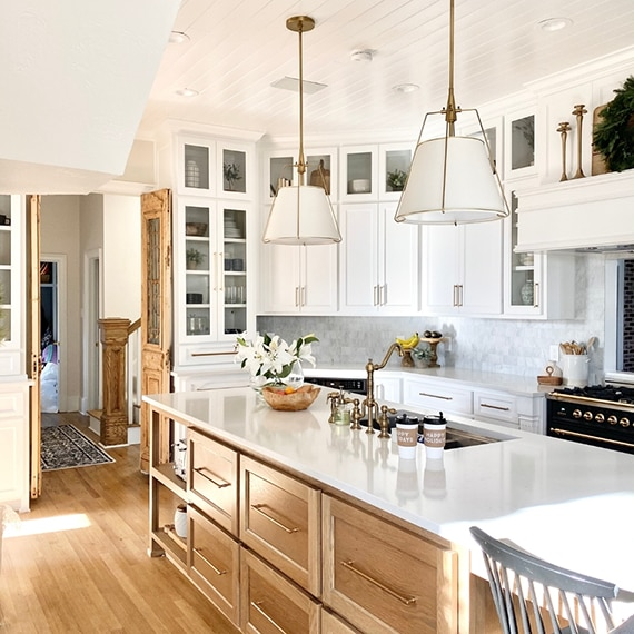 Kitchen with white & glass front upper cabinets, natural wood lower cabinets, white quartz countertop with sink, black & brass gas stove.