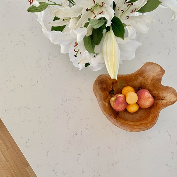 Closeup of white quartz countertop with gray veining, natural wooden bowl holding apples & oranges, and bouquet of white lilies.