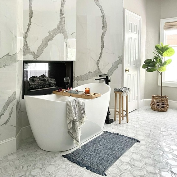 Bathroom with freestanding bathtub, wall-mounted fireplace, white marble look porcelain wall slab with gray veining, and white hexagon marble floor tile.