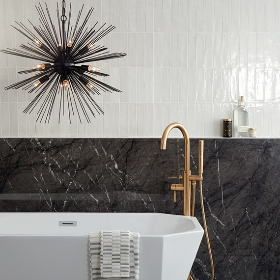 Modern bathroom with soaker bathtub, brushed brass faucet, sunburst chandelier in front of white high-gloss wall tile and black extra-large format porcelain wainscoting.
