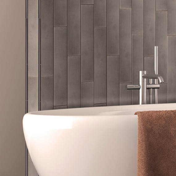 Standalone bathtub and brushed nickel fixtures in front of 3x18 pewter metal wall tile.
