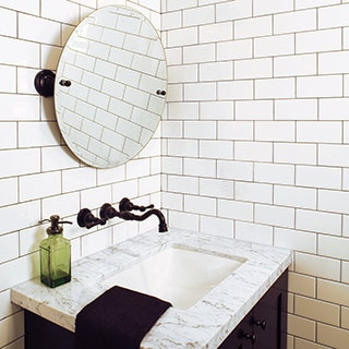 Powder bath with white subway tiled walls with marble topped vanity and black faucet and mirror hardware.