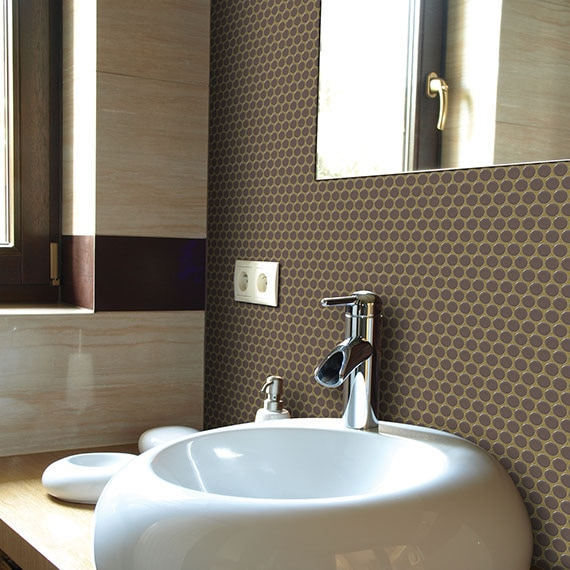 Chocolate colored penny round tiles on a bathroom backsplash with white sink and and small vanity.