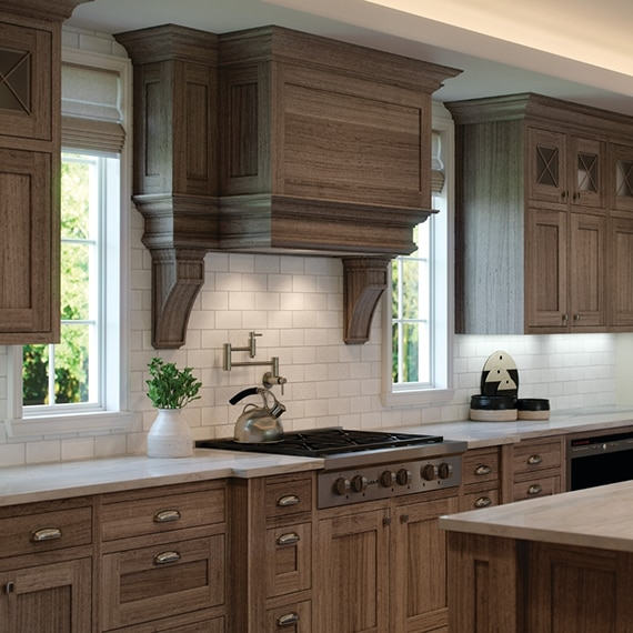 Kitchen with wood-grain cabinets, quartzite countertops, cream, ceramic subway tile, and gas stove with windows on each side.