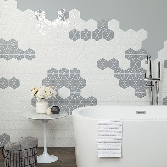 Bathroom feature wall with gray and white six-inch mosaic. Each hexagon is cut into wedges. Soaker tub in the foreground.