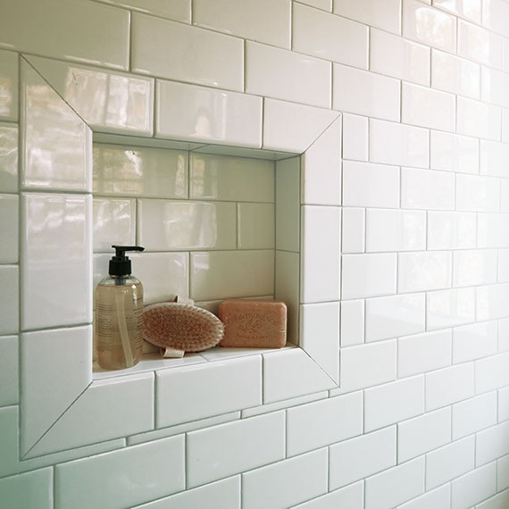 White subway tile on a shower wall with a niche containing bottles.