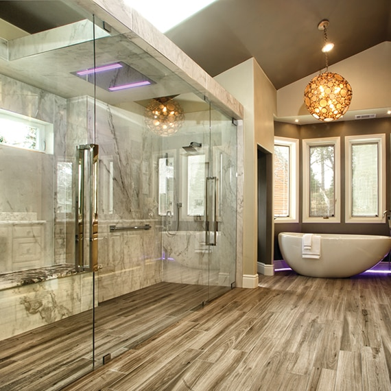 Bathroom with tile floor that looks like wood, large walk-in shower with porcelain slab walls that look like marble, and freestanding tub with globe chandelier.