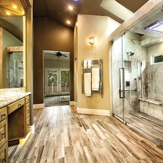 Spacious bathroom with large glass shower on the right wall and long mirrored vanity on the left. Wood-look porcelain tile floor throughout.