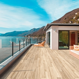 Solarium with wood look tile deck & glass railing overlooking a coastline with blue skies and mountains in the background.