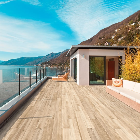 Outdoor space with wood-look porcelain tile deck overlooking a lake with mountains in the distance. House is visible in the background.