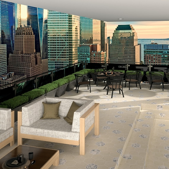 Hotel restaurant with panoramic view of a city skyline, beige hexagon floor tile with white & gray stone look tile accents, tables & chairs, and potted plants along the balcony railing.