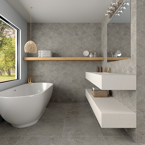 Scandinavian style bathroom with gray floor tile and gray hexagon wall tile that looks like stone, soaker bathtub, and floating white quartz vanity.