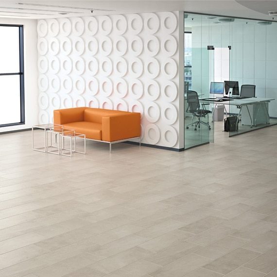 Retro style office foyer with light gray stone look tile flooring, orange sofa, and white feature wall of circle cut-outs.