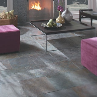 Natural slate 24 by 24 inch tile floors in a living room with lavender sofa, glass-top coffee table, and fire in a fireplace.