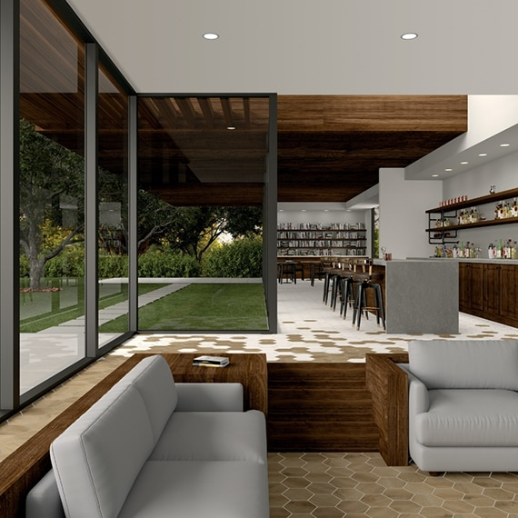 Restaurant lobby with tan stone look hexagon floor tile, gray couches, gray quartz bar top, black barstools, floor-to-ceiling windows revealing lawn and walkway of white pavers.
