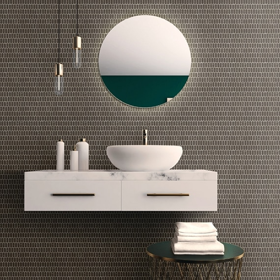 Floating bathroom vanity with white marble countertop, vessel sink, gray mini-picket mosaic tile backsplash, pendant lights, and round mirror.