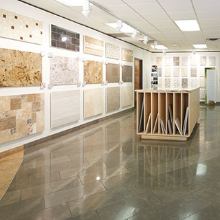 Daltile showroom with workstation and loose tile samples, walls covered by tiled panels of different tiles and patterns.
