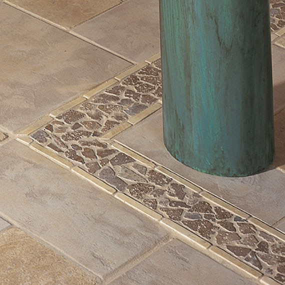 Close up of floor tile with several differnt sized beige rectangular tiles with an accent border of beige pebble style tile.