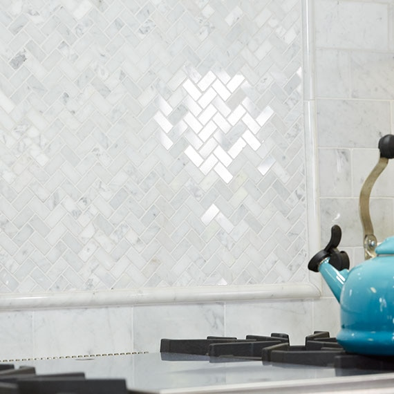 White marble backsplash behind the stovetop with raised pencil trim outline and teal teapot on the stove.