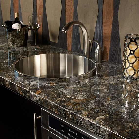 Wet bar with dark granite gray and rust countertop, stainless steel faucet and sink, tan backsplash with black & wood grain accents.