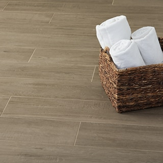Closeup of wood look tile flooring planks with matching grout, natural wicker basket holding 3 rolled white towels.