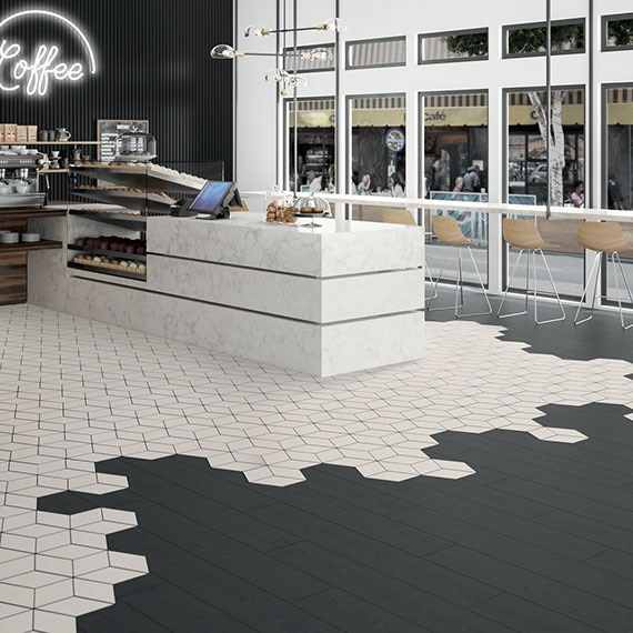 Coffee shop with glass storefront, marble look quartz counter, black wood look tile and white 3D cube tile flooring, white neon coffee sign on black wall.