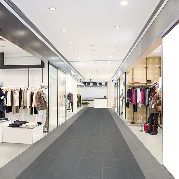 Mall corridor with shops on either side. Wood-look tile on the floor in the corridor in dark grey down the middle of the corridor and light grey on the edges of the corridor.