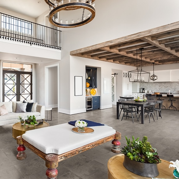 Modern farmhouse living room with stone look tile floor and white furniture, and open kitchen with black table & chairs, and wood beams across the ceiling.