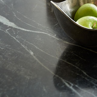 Close up of grey-veined green soapstone countertop with silver bowl of green apples.