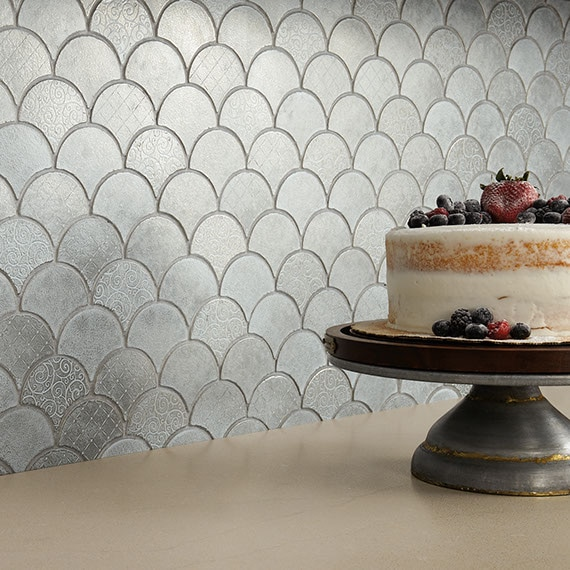 Close up of kitchen backsplash with silver fish scale mosaic tile and smooth beige countertop. Cake on stand with berry decorations sitting on top.
